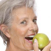Zahnarzt Wunderlich München Grauhaarige Frau mit Apfel hat Implantate
