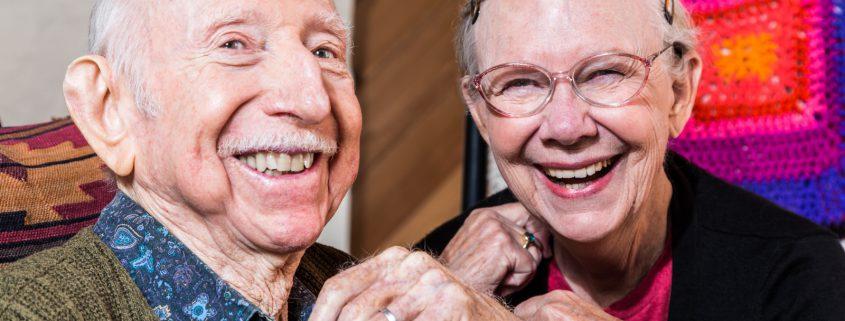 Zahnarztpraxis Wunderlich München Dank Prophylaxe Älteres Paar lacht mit gesunden Zähnen in die Kamera